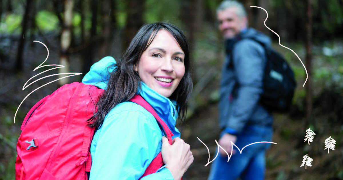 A woman shoulders her backpack as she and the man in the background set off for a hike.